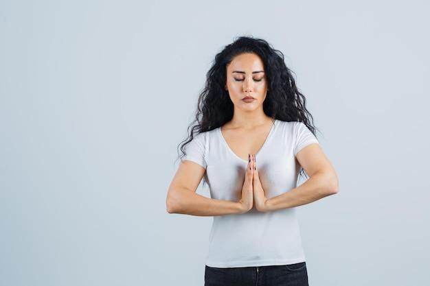 Jonge brunette vrouw in een wit t-shirt aan het bidden