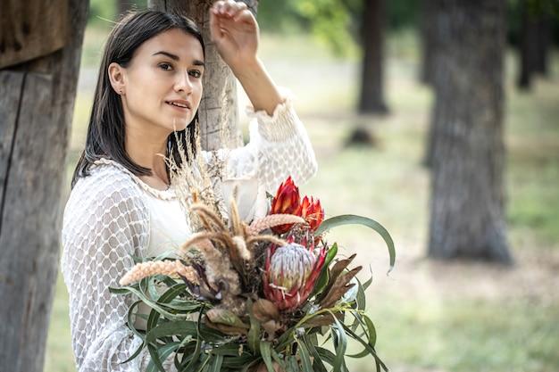 Jonge brunette vrouw in een witte jurk met een boeket bloemen in het bos op een onscherpe achtergrond, kopieer ruimte.