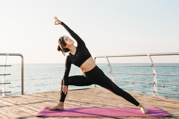 Jonge brunette vrouw in een zwarte jumpsuit het beoefenen van yoga op het strand bij zonsopgang. concept van wellness en een gezonde levensstijl.
