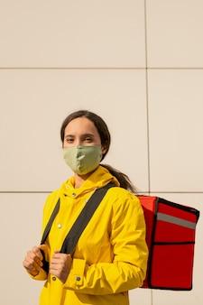 Jonge brunette vrouw in gele jas en masker op zoek naar jou