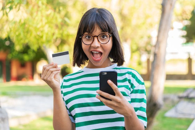 Jonge brunette vrouw in het park die met de mobiel koopt en een creditcard vasthoudt met een verbaasde uitdrukking