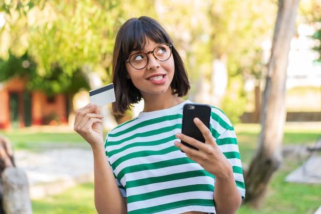 Jonge brunette vrouw in het park kopen met de mobiel met een creditcard terwijl ze denken