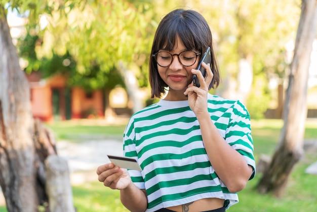 Jonge brunette vrouw in het park kopen met de mobiel met een creditcard