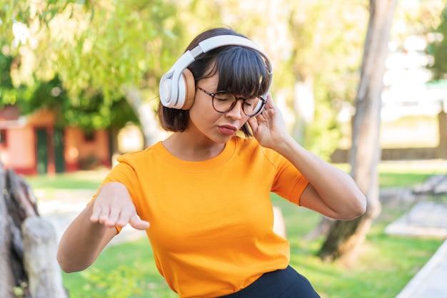 Jonge brunette vrouw in het park muziek luisteren en dansen