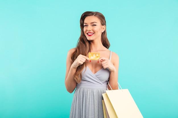 Jonge brunette vrouw in jurk met winkelen pakketten en gouden creditcard in handen, geïsoleerd over blauwe muur