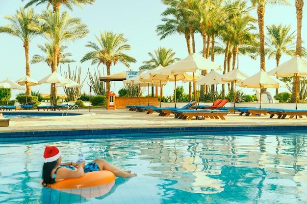 Jonge brunette vrouw in kerstman hoed in een cirkel zwemmen in het zwembad in de kerstvakantie op de achtergrond van palmbomen.