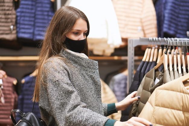 Jonge brunette vrouw in medische masker kiest kleding in de winkel en maakt aankopen