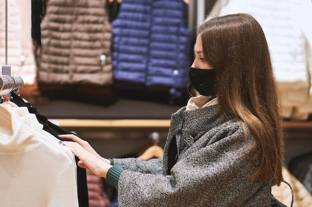 Jonge brunette vrouw in medische masker kiest kleding in de winkel en maakt aankopen Premium Foto
