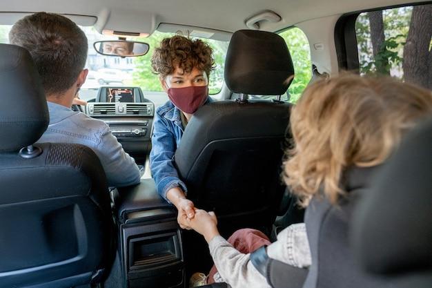 Jonge brunette vrouw in vrijetijdskleding en beschermend masker met de hand van haar zoontje op de achterbank zittend in de auto door haar man