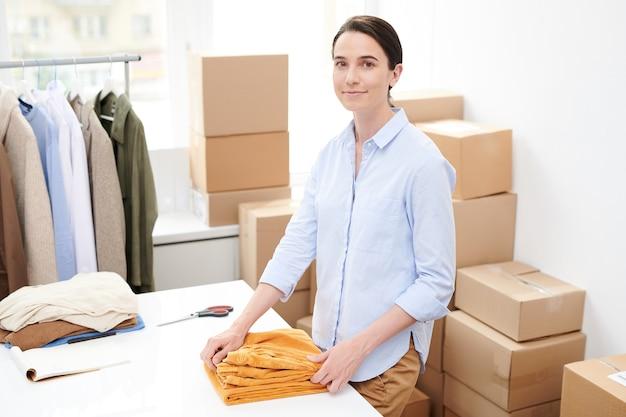 Jonge brunette vrouw in vrijetijdskleding op zoek naar jou terwijl torusers vouwen voor verpakking door bureau