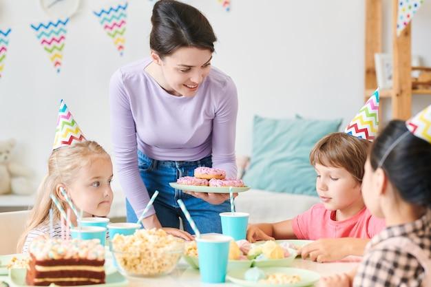 Jonge brunette vrouw in vrijetijdskleding plaat met donuts te houden tijdens het kijken naar groep kleine kinderen thuis verjaardagsfeestje