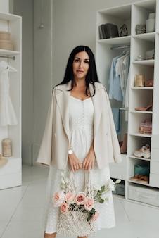 Jonge brunette vrouw in witte jurk en jasje met een boeket bloemen in de studio