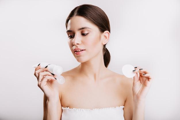 Jonge brunette vrouw in witte top kijkt naar vochtinbrengende gezichtscrème. portret van model poseren op geïsoleerde muur.