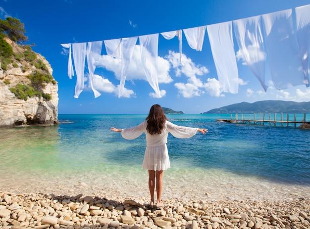 Jonge brunette vrouw in witte zomerjurk staande op het strand en kijkend naar de zee.