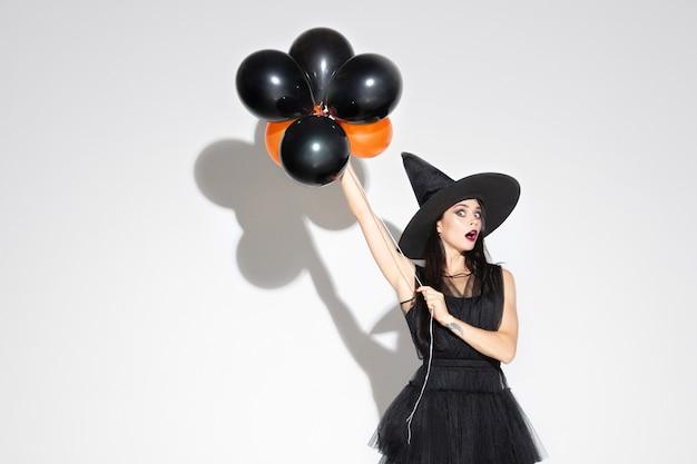 Jonge brunette vrouw in zwarte hoed en kostuum op wit
