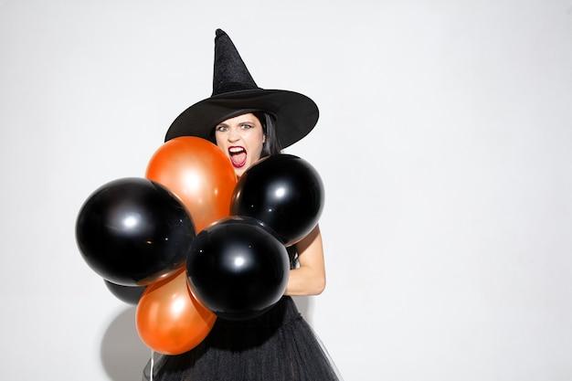 Jonge brunette vrouw in zwarte hoed en kostuum op witte achtergrond. aantrekkelijk kaukasisch vrouwelijk model. halloween, zwarte vrijdag, cybermaandag, verkoop, herfstconcept