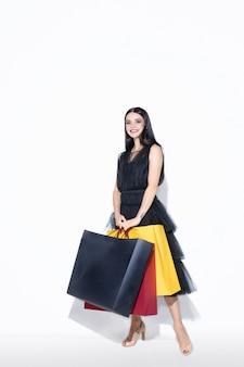 Jonge brunette vrouw in zwarte jurk winkelen op witte muur.