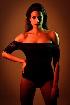 Jonge brunette vrouw in zwarte lingerie met rode en groene verlichting.