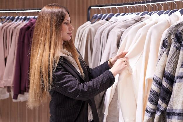 Jonge brunette vrouw kiest kleding en accessoires in de winkel