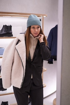 Jonge brunette vrouw kiest kleding en accessoires in de winkel Premium Foto