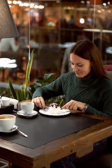 Jonge brunette vrouw koffie drinken in een café en dessert eten