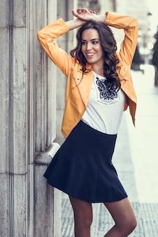 Jonge brunette vrouw lachend in stedelijke achtergrond.