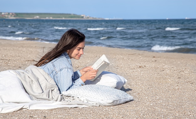 Jonge brunette vrouw ligt aan zee op het strand bedekt met een deken, en leest een boek. gezellige sfeer op het strand, zomerconcept.