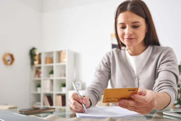 Jonge brunette vrouw met creditcard zittend aan tafel en het opschrijven of controleren van uitgaven in voorbeeldenboek