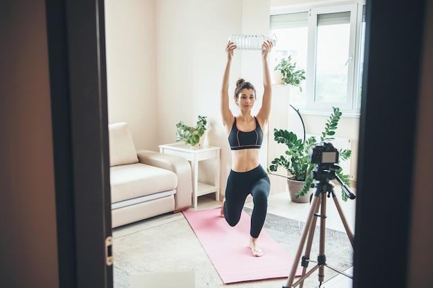 Jonge brunette vrouw met een fles water traint thuis sportkleding dragen voor camera