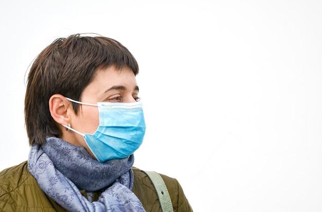 Jonge brunette vrouw met kort haar in profiel in bovenkleding met medisch masker op gezicht op witte muur. p.