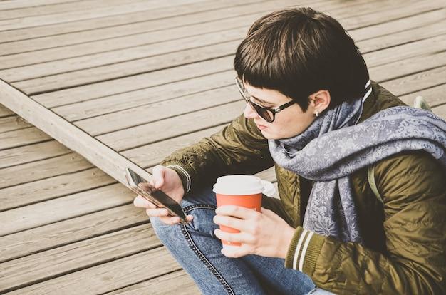 Jonge brunette vrouw met kort haar in spijkerbroek en jas zit op houten pier met kopje koffie in haar handen en kijkt naar het telefoonscherm. verslaving aan gadgets. gestileerd afgezwakt beeld met zachte focus