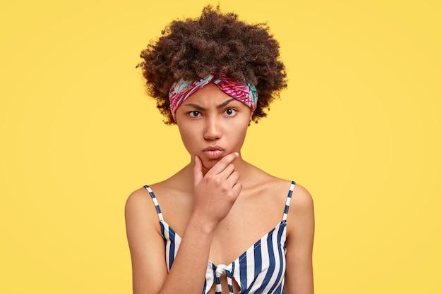 Jonge brunette vrouw met krullend haar en kleurrijke bandana