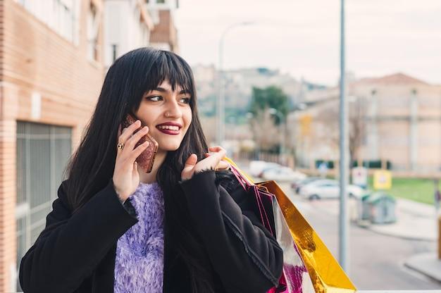Jonge brunette vrouw met lang haar en groene ogen bellen na het winkelen. boodschappentassen. granaatkleurige lippen. concept van winkelen.