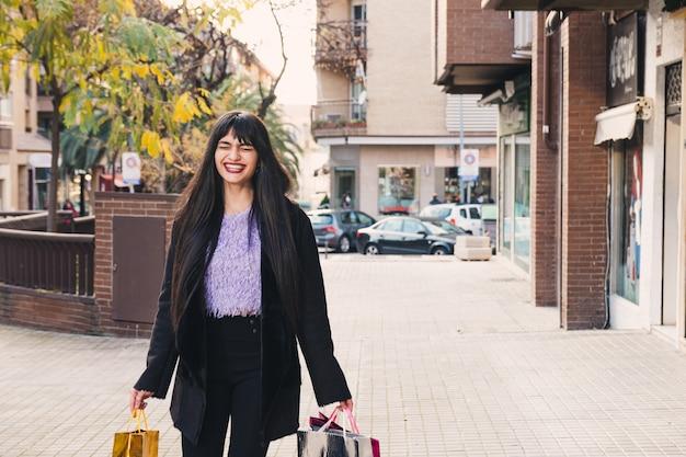 Jonge brunette vrouw met lang haar en groene ogen wandelen met boodschappentassen. lachend. winkelen concept.
