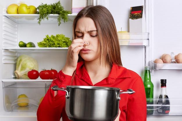Jonge brunette vrouw met ontevreden uitdrukking ruikt bedorven soep in stoofpot pan, voelt muffe geur thuis keuken, staat tegen koelkast.