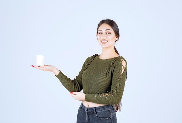 Jonge brunette vrouw met plastic beker en gelukkig poseren.
