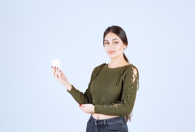 Jonge brunette vrouw met plastic beker en poseren.