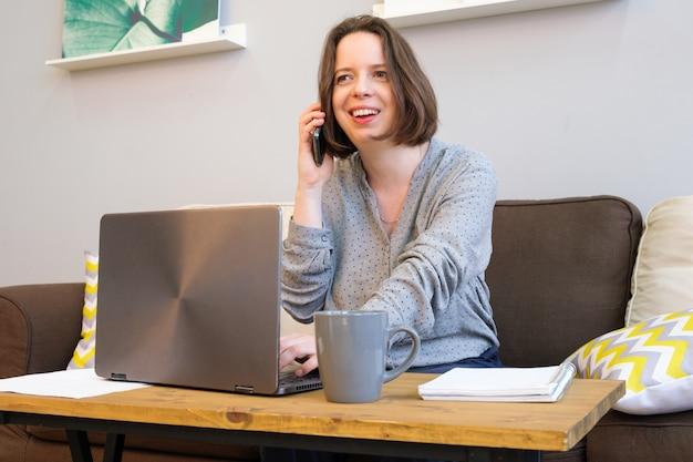 Jonge brunette vrouw met schouderlang haar lacht terwijl ze aan de telefoon praat. een vrouw zit thuis op de bank voor een tafel met een laptop met een kopje koffie. thuiswerken op afstand
