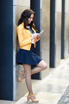 Jonge brunette vrouw met smartphone in stedelijke achtergrond.