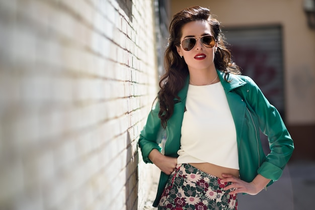 Jonge brunette vrouw met zonnebril in stedelijke achtergrond
