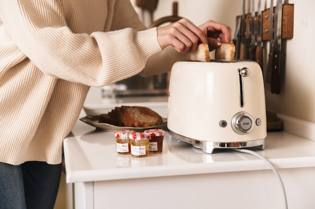 Jonge brunette vrouw ontbijt met toast en jam in de keuken thuis maken