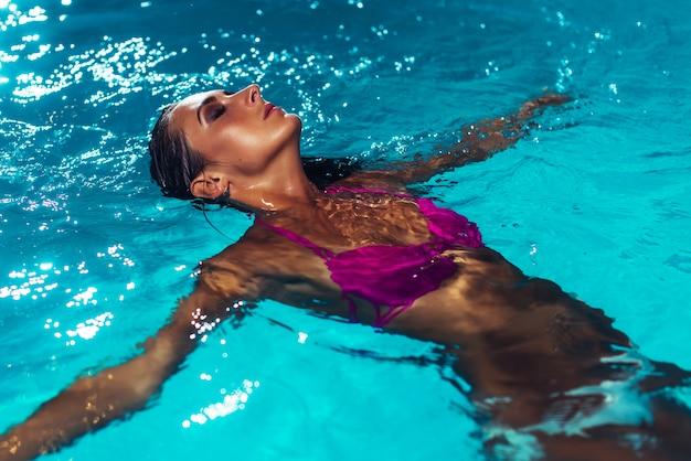 Jonge brunette vrouw ontspannen in het zwembad.