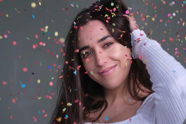 Jonge brunette vrouw regent confetti. natuurlijk licht. concept feestviering