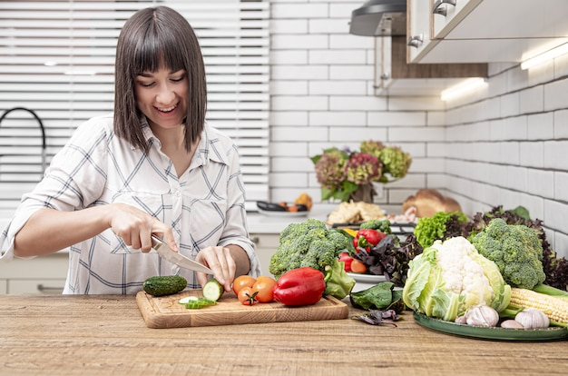 Jonge brunette vrouw snijdt groenten op salade op moderne keuken binnenruimte.