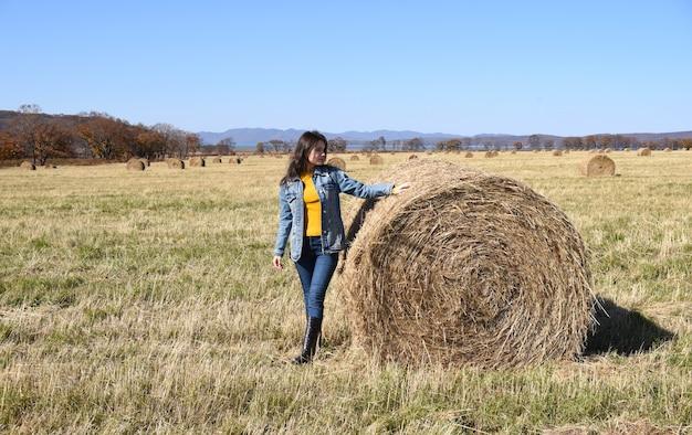 Jonge brunette vrouw staande in de buurt van hooiberg in veld met balen hooi
