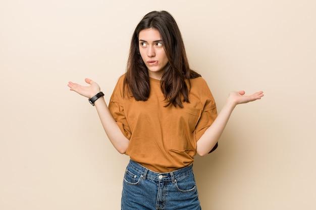 Jonge brunette vrouw tegen een beige achtergrond verward en twijfelachtig schouders ophalen