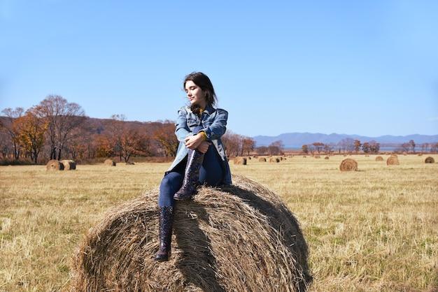 Jonge brunette vrouw zit bovenop hooiberg in veld