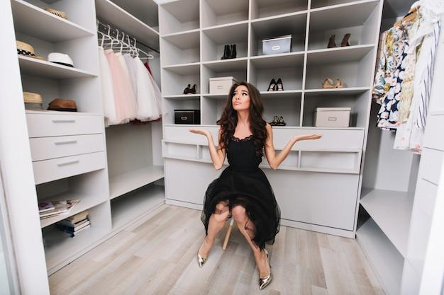 Jonge brunette vrouw zit in een enorme kleedkamer denkt na over de keuze van kleding, ze is gekleed in stijlvolle zwarte outfit en zilveren schoenen, waarbij ze echte positieve gezichtsemoties uitdrukt.
