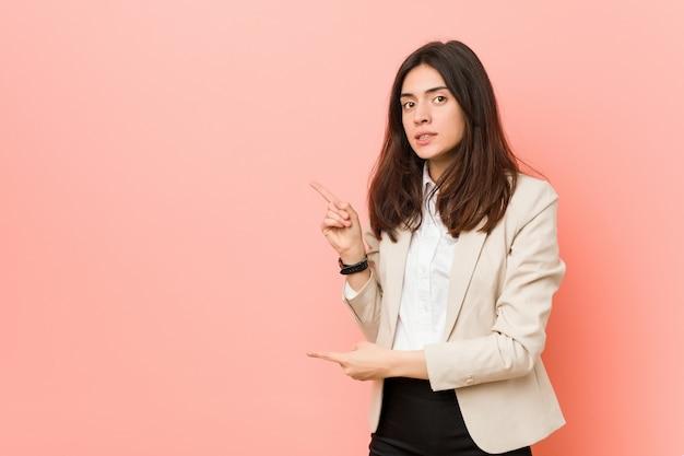 Jonge brunette zakenvrouw geschokt wijzend met wijsvingers