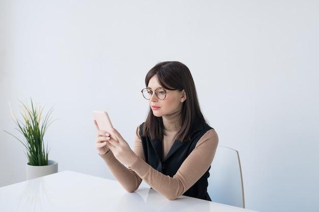 Jonge brunette zakenvrouw in smart casual scrollen in smartphone zittend door balie in kantoor